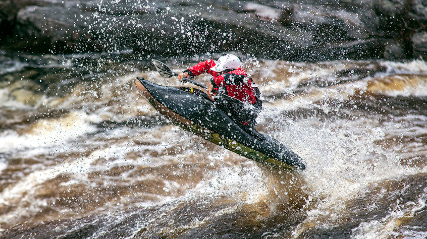 Ben Marr in helmet and dry suit fro Sweet Protection kayaks down the river | Sweet Protection