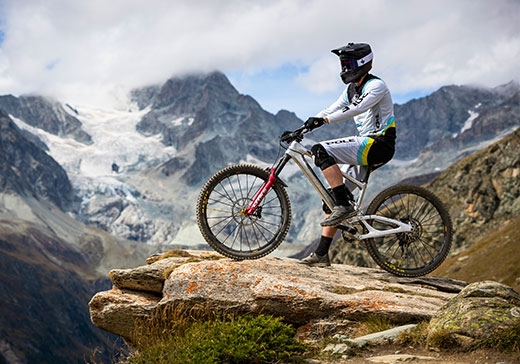 A man in an Arbitrator helmet from Sweet Protection on a bicycle stands on top of a cliff | Sweet Protection