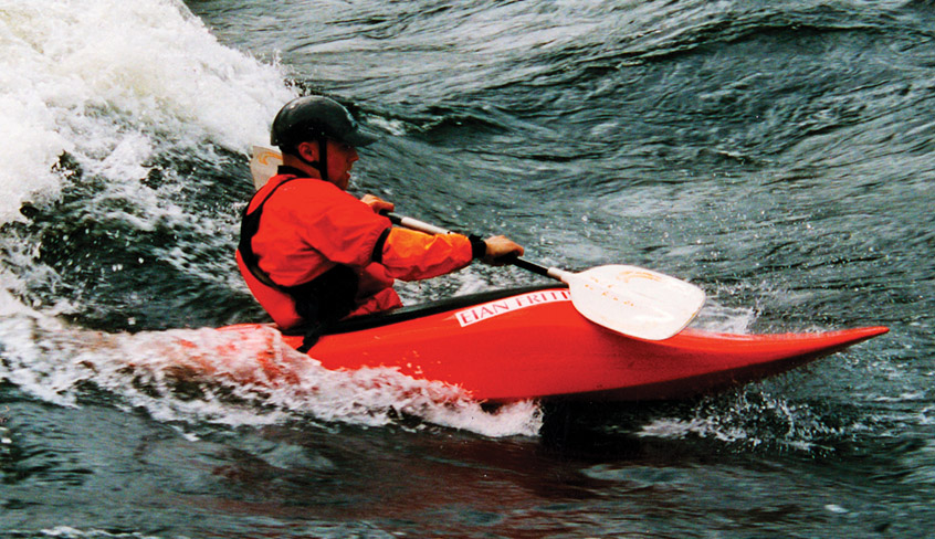 A man in helmet and dry suit from Sweet Protection kayaks down the river.