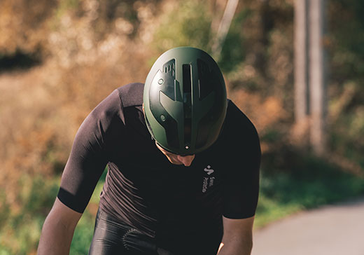 Man with bicycle in the forrest with bicycle clothes and bicycle helmet from Sweet Protection