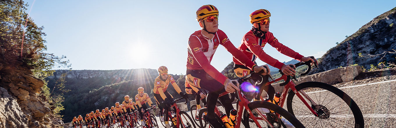 Uno-X | Four cyclists in sportswear, Falconer helmets and raske briller fra Sweet Protection ride bicycles.