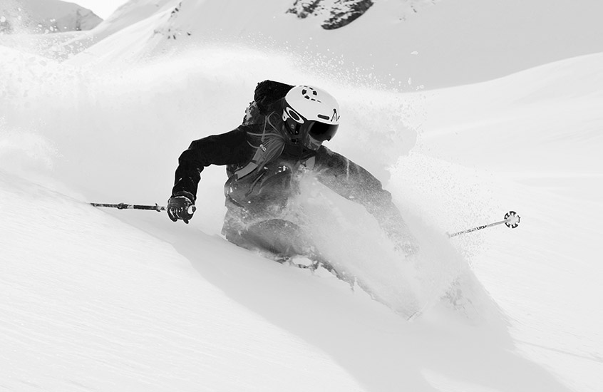 A man in an Igniter II helmet is skiing down the mountain.