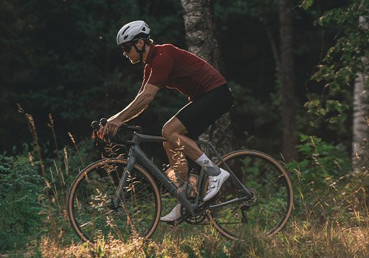 Man on a bicycle in the forrest with bicycle clothes and bicycle helmet from Sweet Protection