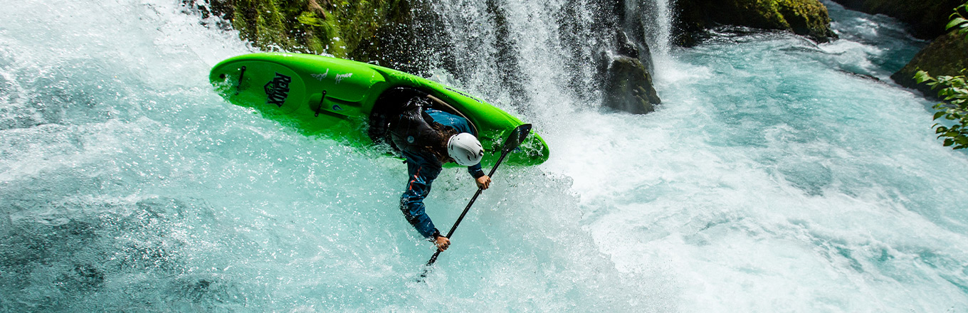 A man in paddlesport helmet on kayaks goes down the river.