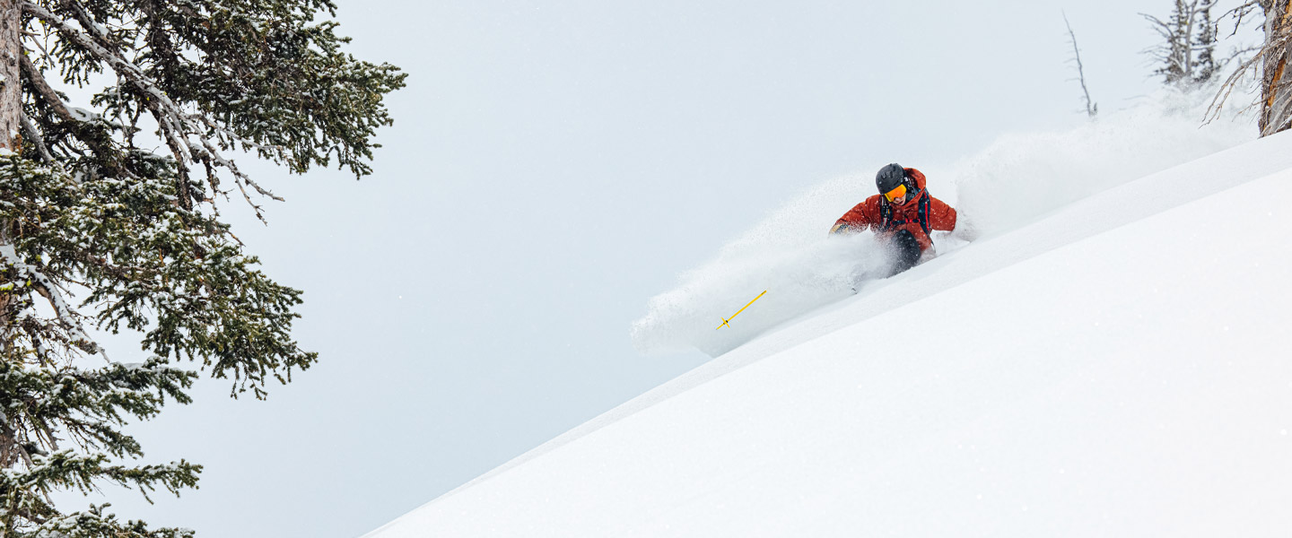 A man in Sweet Protection clothes, helmet and goggles is skiing.