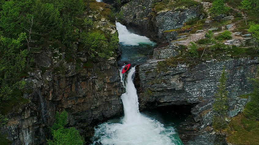 Paddlesports - A man on kayaks goes down the waterfall. | Sweet Protection