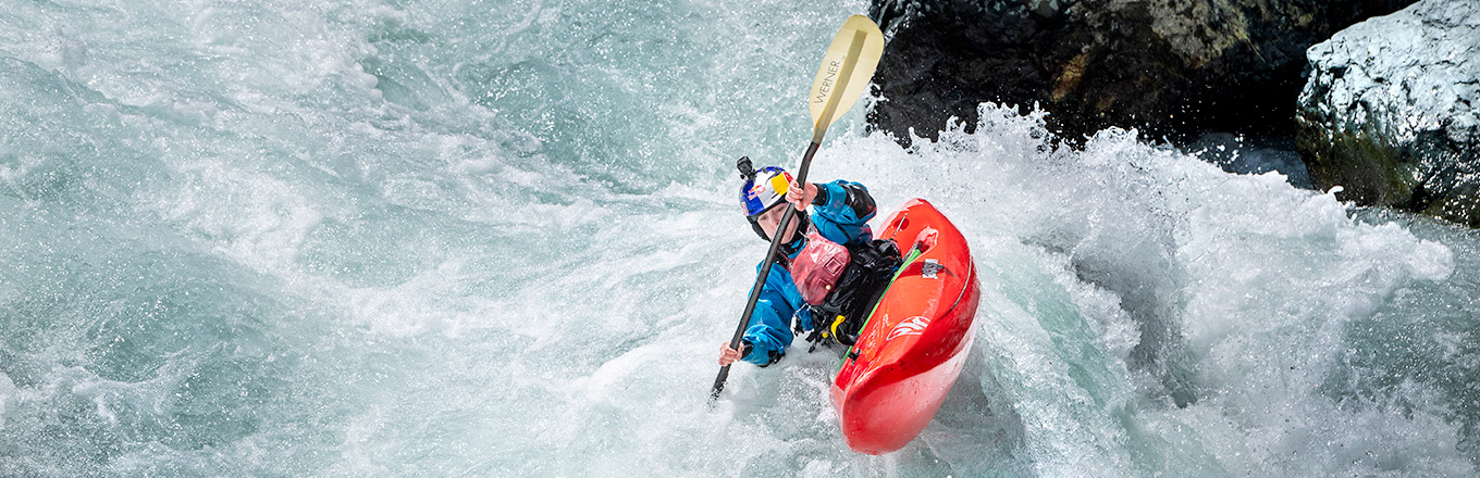 Nouria Newman in a helmet and a dry suit is kayaking down the river | Sweet Protection | Ali Bharmal / Red Bull Content Pool©