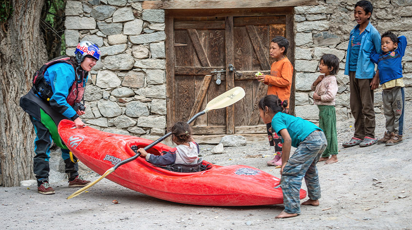 Nouria Newman in a dry suit and paddlesport helmet shows her kayaks to the kids | Sweet Protection