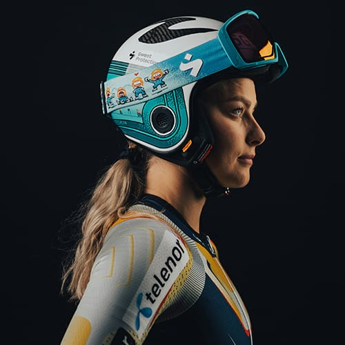A woman wearing a Volata Mips Team Edition Helmet and Clockwork RIG Reflect Team Edition goggles from Sweet Protection.