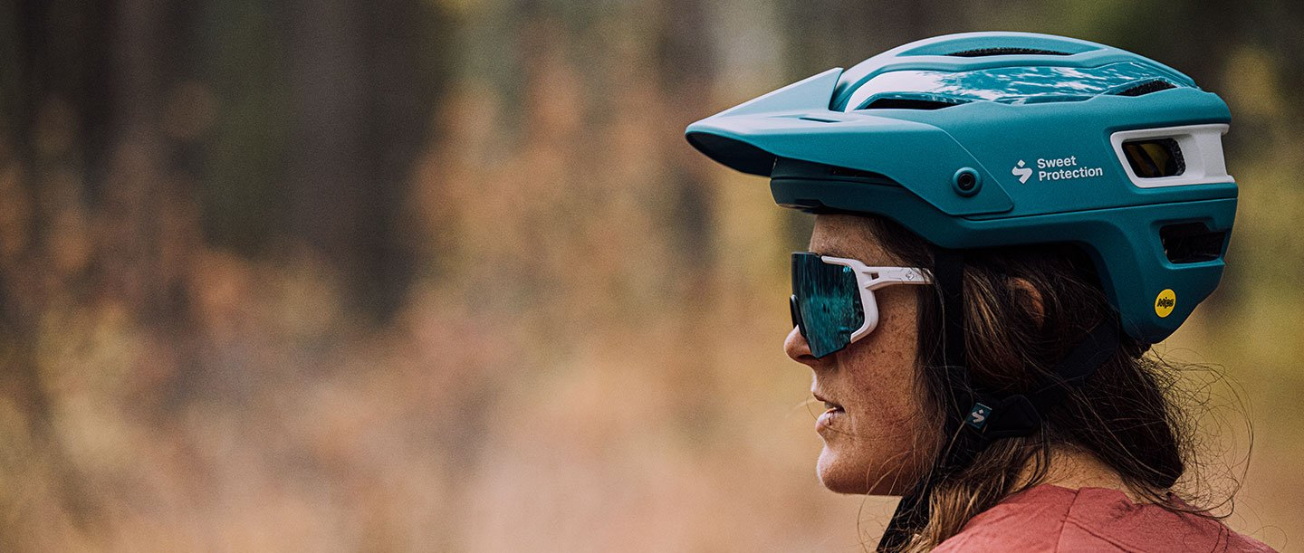 A woman in helmet and Ronin sunglasses from Sweet Protection.