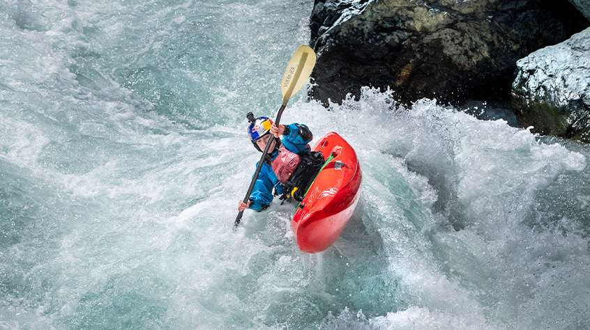 Nouria Newman in helmet and dry suit fro Sweet Protection kayaks down the river | Sweet Protection